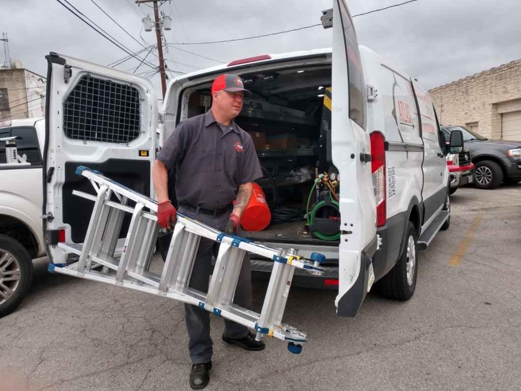 HVAC tech carrying ladder from AC company van