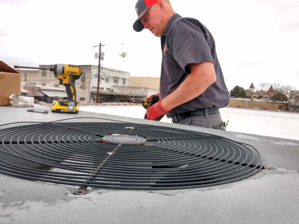 HVAC technician working on air conditioning unit on rooftop