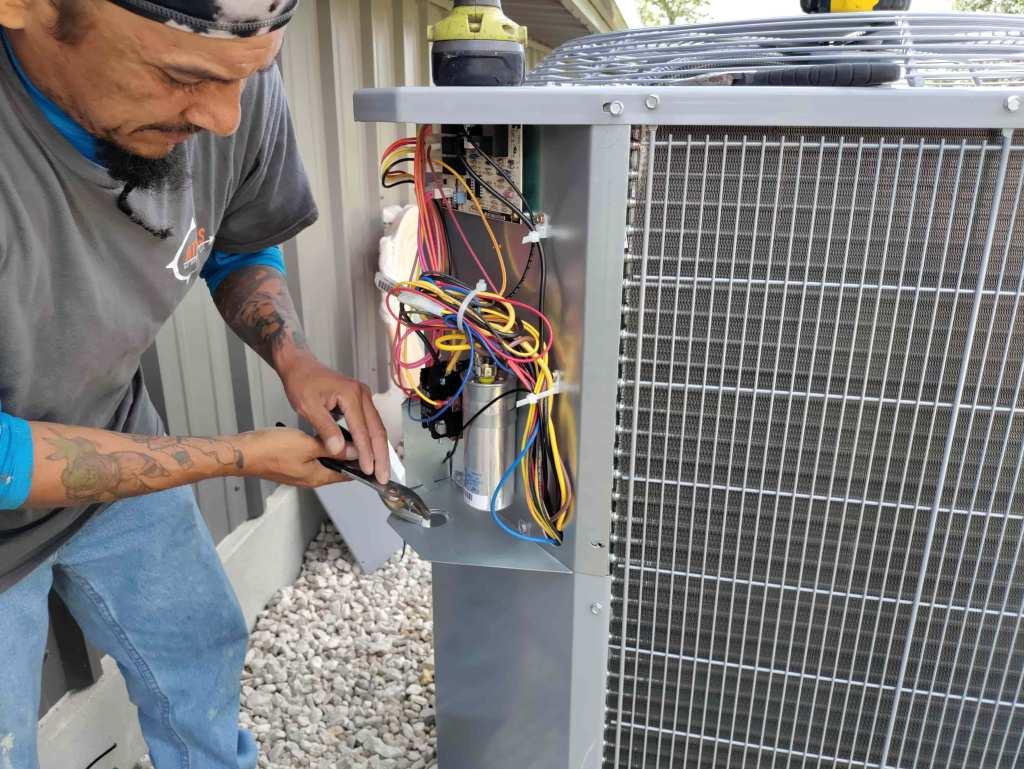 technician installing outdoor AC condenser
